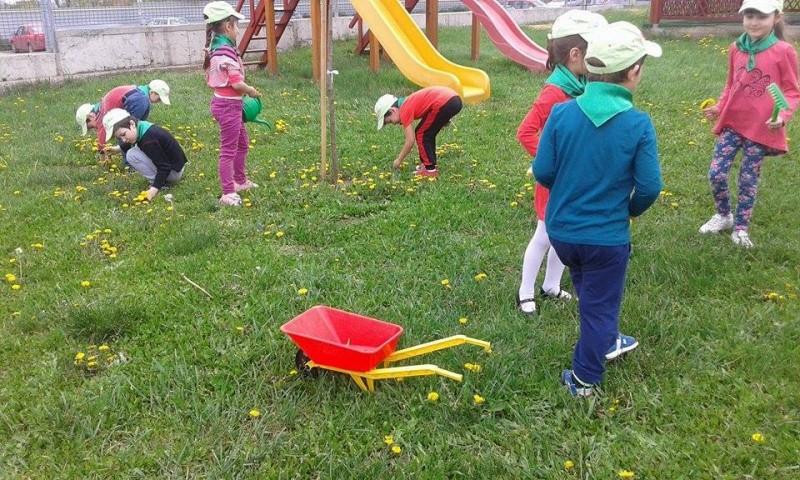 Copii au grija de curtea gradiniței.