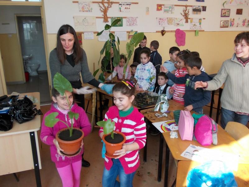 Invatatoarea Dubei Viorica indruma elevii in actiunea de ingrijire a florilor din clasa.