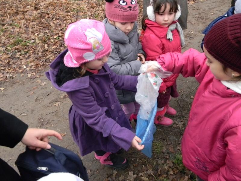 Copiii colectează și sortează gunoiele în saci menajeri